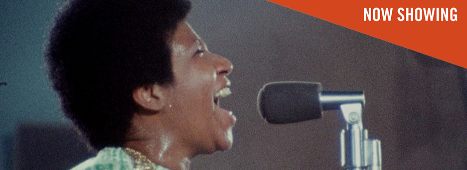 A close up picture of soul singer Aretha Franklin as she is singing into the microphone. A still from the documentary Amazing Grace.