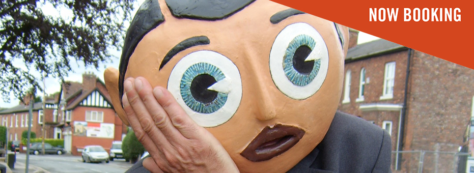 A man in a big, comical caricature head mask rests his cartoonish head on his hand. He wears a smart suit. This image is a still from Being Frank: The Chris Sievey Story