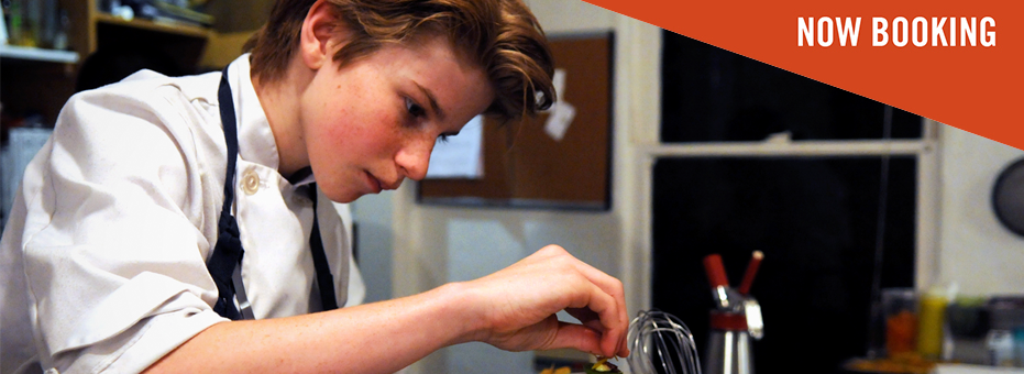 A young boy with mid-length blonde hair leans over a professional kitchen counter. He sprinkles salt with great concentration onto his dish. A sticker in the corner says 'Now Booking' on this still from Chef Flynn.