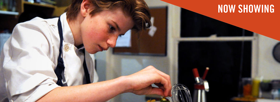 A young boy with mid-length blonde hair leans over a professional kitchen counter. He sprinkles salt with great concentration onto his dish. A sticker in the corner says 'Now Showing' on this still from Chef Flynn.