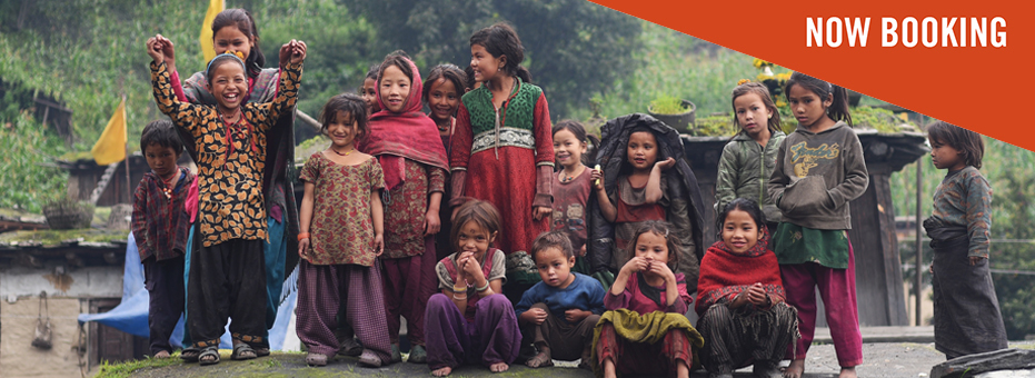 A group of young Nepalese children pose for a photograph together in a remote, hilly village. They smile happily, and throw up their hands in this image from Children of the Snow Land.