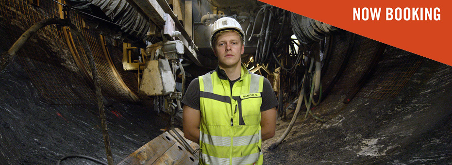Man standing in a tunnel. He is facing the camera, wearing a high-vis jacket and a white helmet.