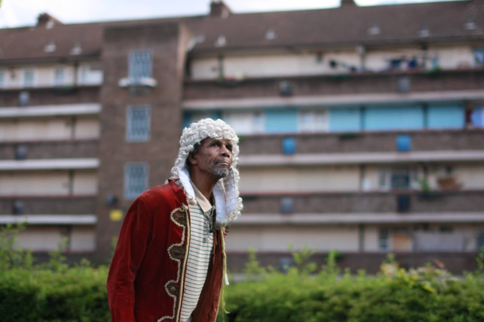 An unusual image of a Black British man standing in 18th-century dress, with a long, bright white wig on; behind him is what looks like a modern council estate. He looks to one side, as if round the camera.