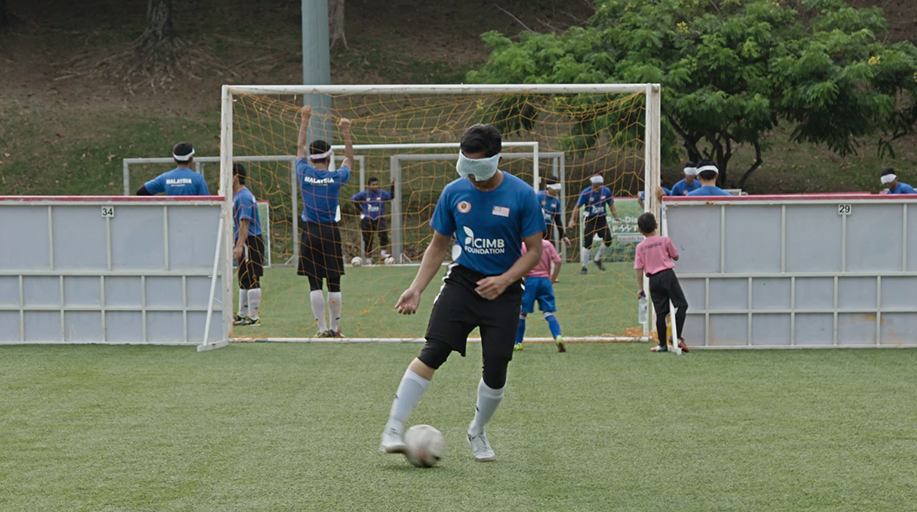 A young Malaysian boy in a blue football kit stands in the middle of a pitch, with a goal behind him and a blindfold on his face. At his feet is a football, and behind him are other players. The image is from the film Eye on the Ball.