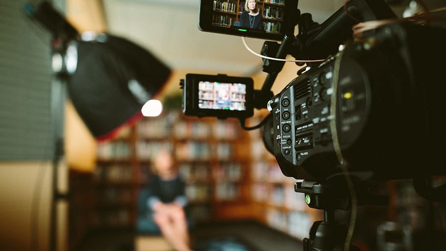 In the foreground is a camera that films a woman sitting in front of a large, filled bookshelf. The woman and the bookshelf are blurry, and the focus is on the camera.