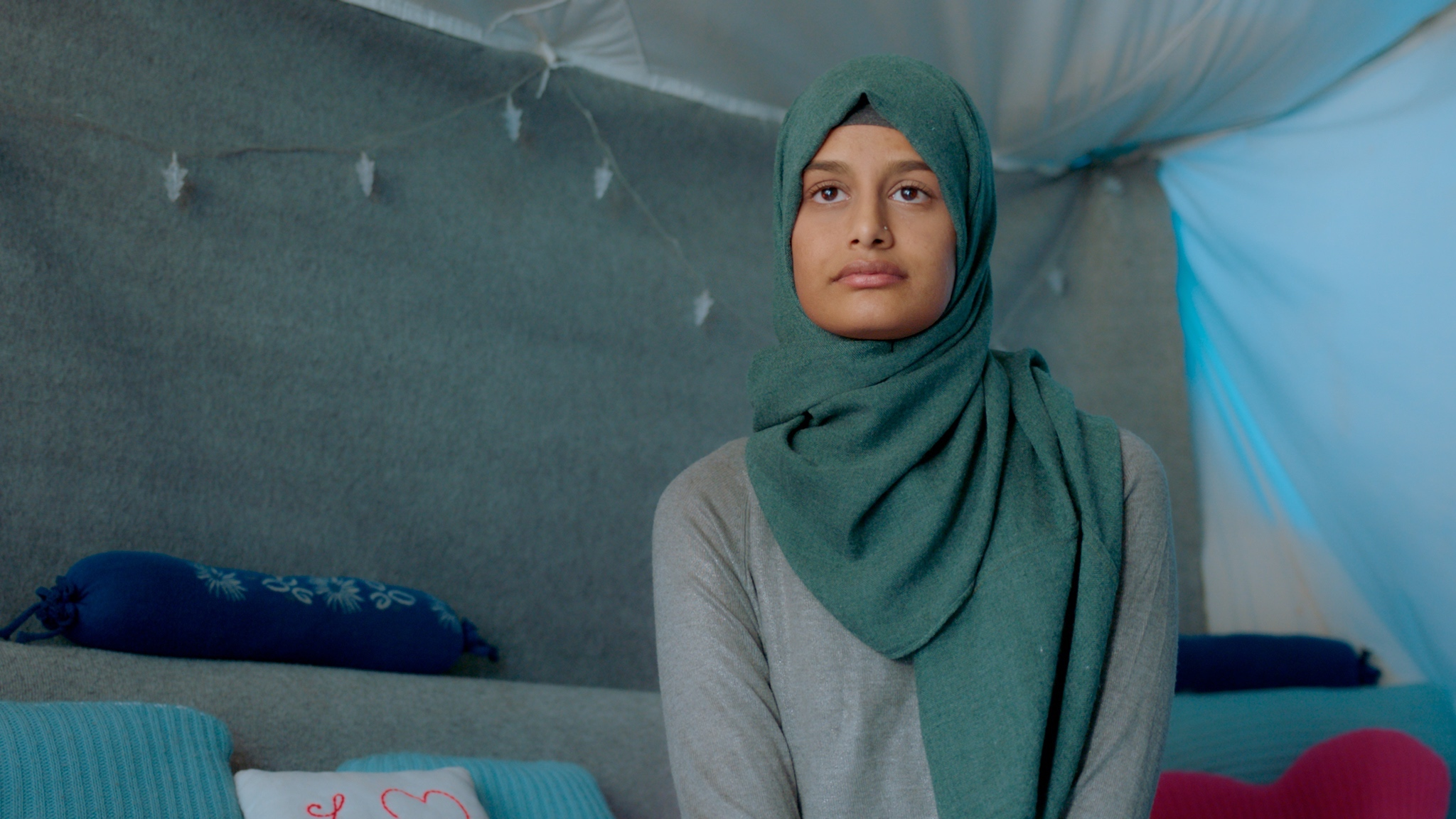 A young woman, Shamima Begum, sits in a tent-like room. We see her from the waist up. She is wearing a long-sleeved grey top and a teal headscarf. This is an image from Alba Satorra's documentary, The Return: Life After ISIS.