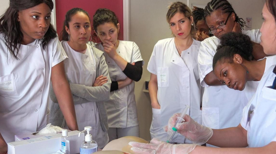 Image of a group of seven young women in white nursing uniforms watching another nurse demonstrate something with a needle. A still from the documentary Each and Every Moment.