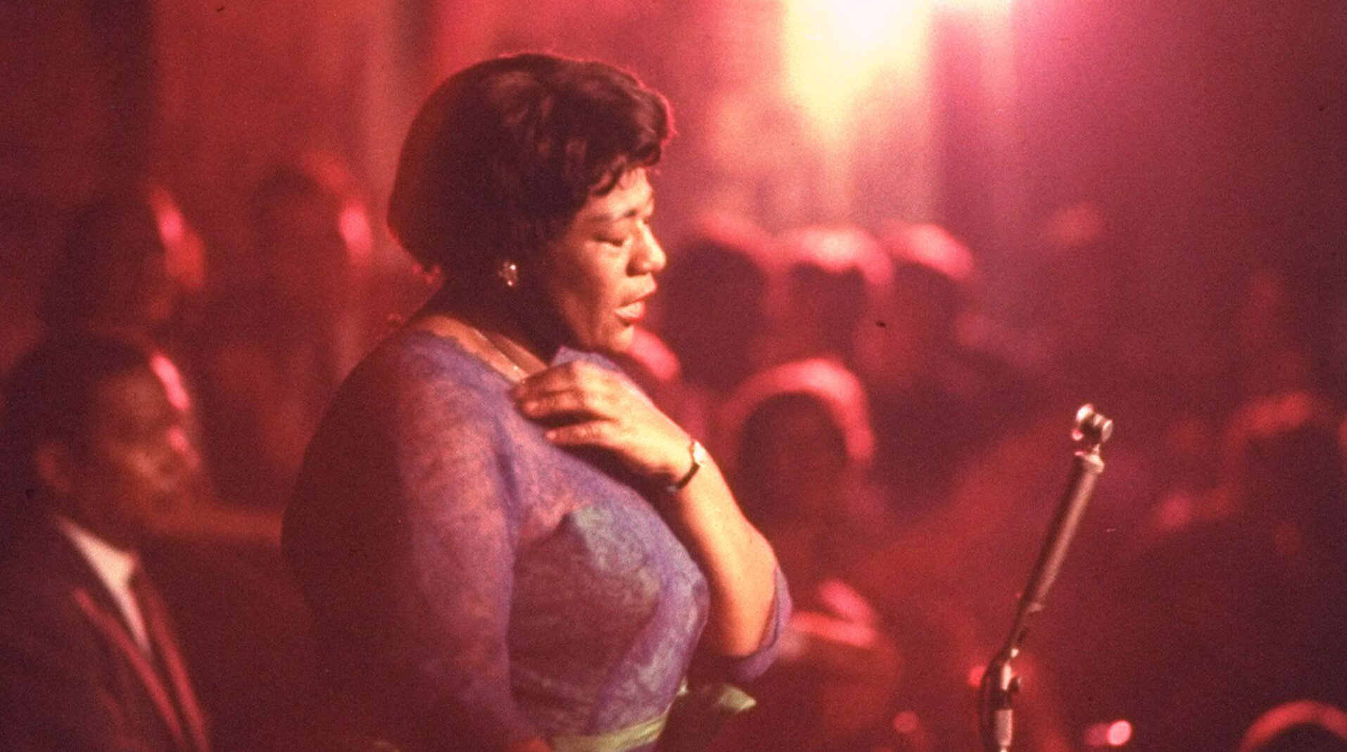 Image of Ella Fitzgerald singing into a microphone on stage. A still from the documentary Ella Fitzgerald: Just One Of Those Things