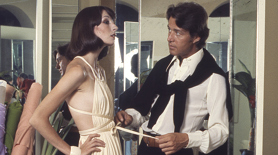 Photograph of designer Halston dressing a model. A still from the documentary Halston.