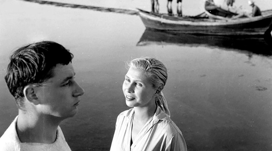 Black and white image of a woman looking at a man as they stand in front of a river with a boat in the background. A still from Agnes Varda's La Pointe Courte