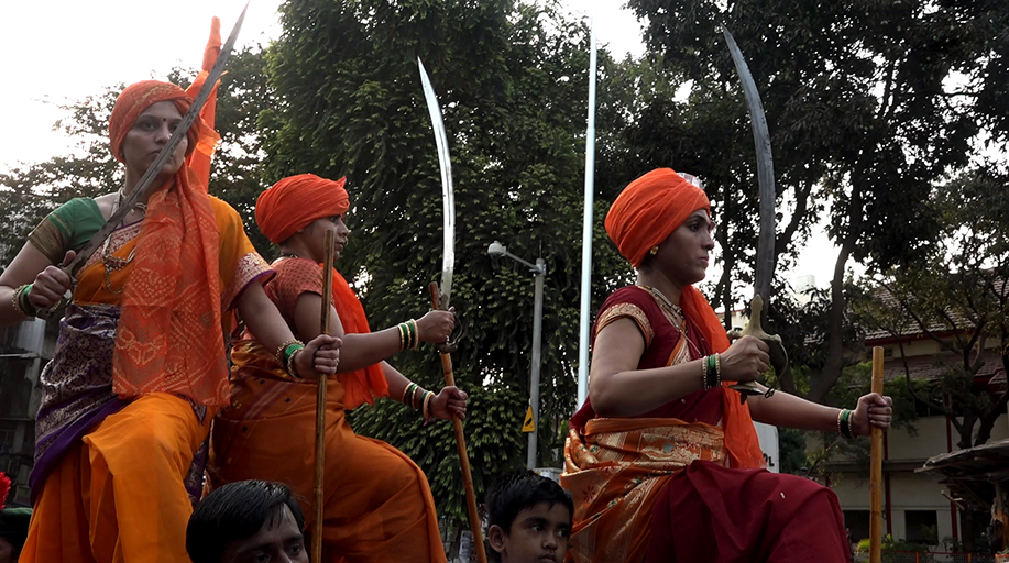 An image of three women in Indian cultural dress with swords. A still from the documentary Reason.