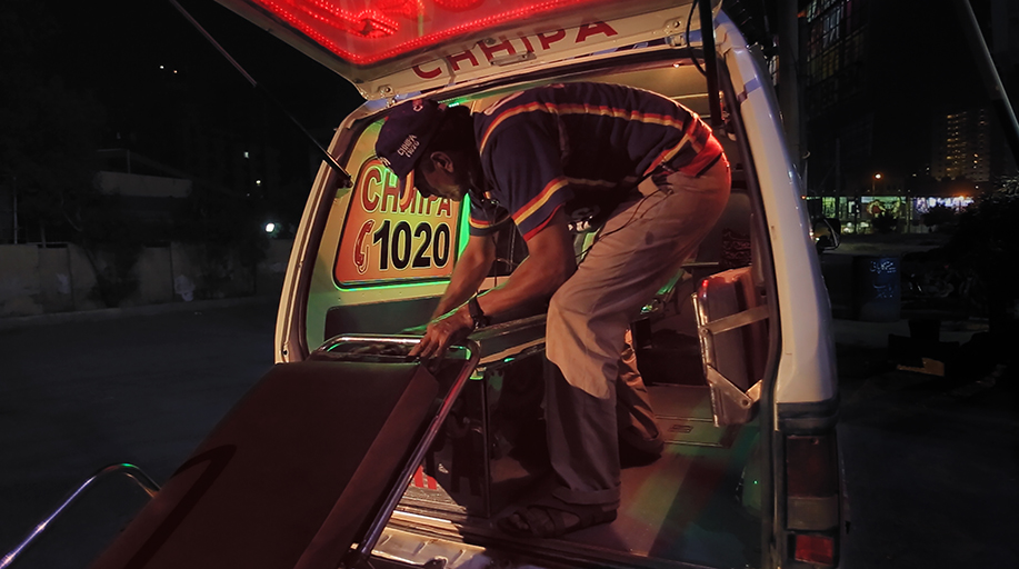 Image of a male paramedic placing a stretcher into an Indian ambulance. A still from the documentary This Shaking Keeps Me Steady.