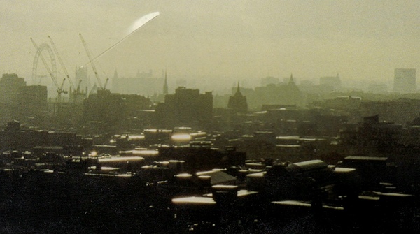 A retro, atmospheric panoramic picture of the London skyline. The buildings stand like dark silhouettes on the horizon, with cranes in the distance. The sun reflects brightly off their roofs, and the sky is thick with hazy smog.