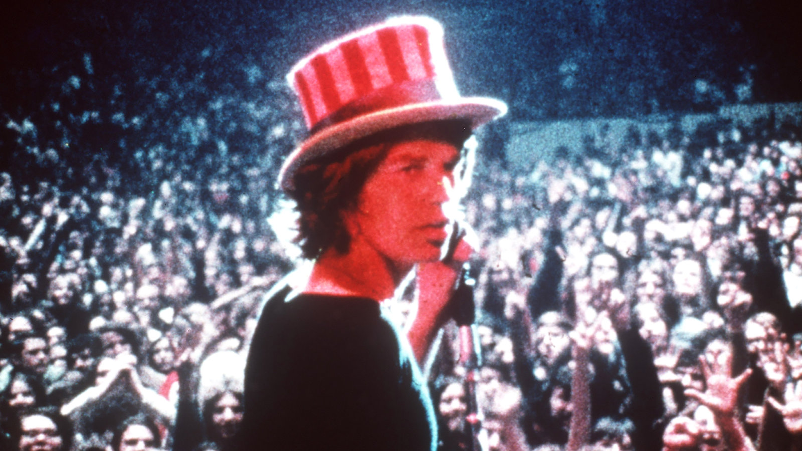 Wearing a stripey hat that resembles the American flag, the singer Mick Jagger turns to face a camera. In his hand is a microphone, and behind him is a huge crowd. The image is from Gimme Shelter, a film you can choose to see in DocHouse's RE:DOX strand.