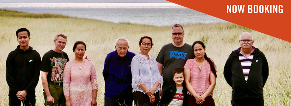 With the sea in the background, a family stand in a Danish field of long grass. The men are almost all white, and the women are all Thai. The image is from the documentary Heartbound.