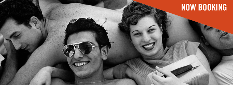 A black and white photo of a group of American teenagers, all lying together on a beach, from Last Stop Coney Island: The Life and Photography of Harold Feinstein. A man and a woman in trendy sunglasses lie on their friend's back, and smile.