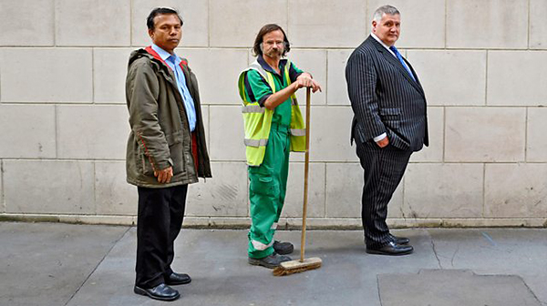 Against a building's plain white wall stands three men. On the left is a British Asian man, dressed in casual clothes. In the middle is a skinny, white man in a road sweeper's uniform, and he leans on a broom. On the right is a portly white man in a suit.