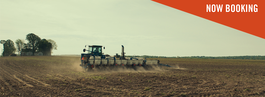 An observational, distant shot of a large mechanical plough working a big field in this still from Frederick Wiseman's Monrovia, Indiana.