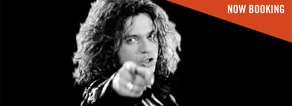 A black and white photo of a handsome white man with long curly hair in a leather black coat. He looks directly into the camera, and in the foreground is his blurry finger pointing down the lens of the camera.