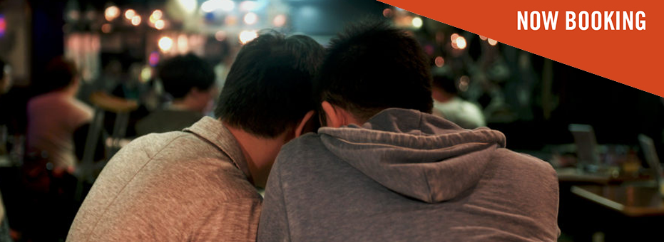 Two men huddle together on a bench in what looks like an outside space next to a busy bar. It's night time, and the streetlights in the distance look blurry. In the top right corner is a 'Booking Now' sign on this still from Of Love & Law.