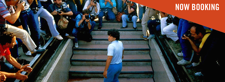 The famous football star Diego Maradona is wearing blue as he walks up the stairs towards a football pitch. There is a crowd of photographers surrounding him. This is a still from the documentary Diego Maradona.