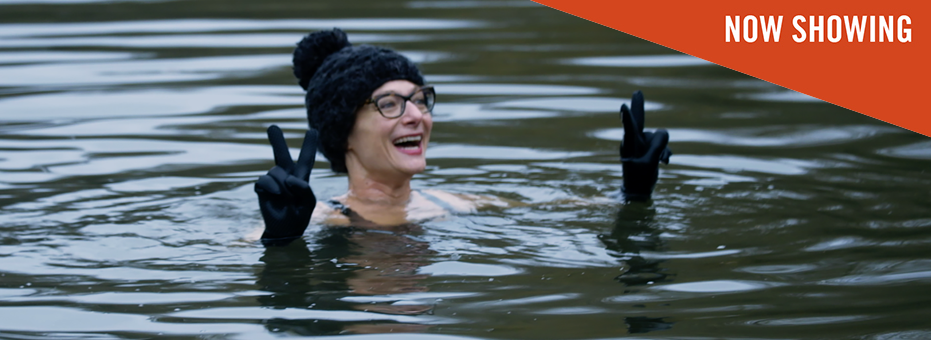 In a chilly looking pond in Hampstead Heath, a middle-aged white woman with glasses pops her head out of the water and poses with two peace signs for the camera. The still is from British documentary The Ponds, showing at Bertha Dochouse.