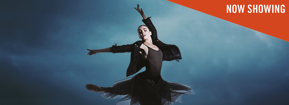 The famous ballerina, Natalia Osipova is dancing in front of a blue background. This is a still from the documentary Force of Nature Natalia.