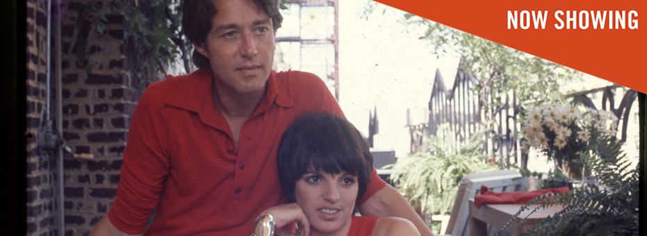 The famous american fashion designer, Roy Halston is sitting on a bench with singer Liza Mineli. They are both wearing red.This is a still from the documentary Halston.