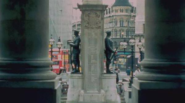 An old image of a war memorial. The edges of the image are filled with two big, dark columns of a grand building. Out in front of us, we see a plinth with names on it, and on either side stands statues of soldiers facing outwards.