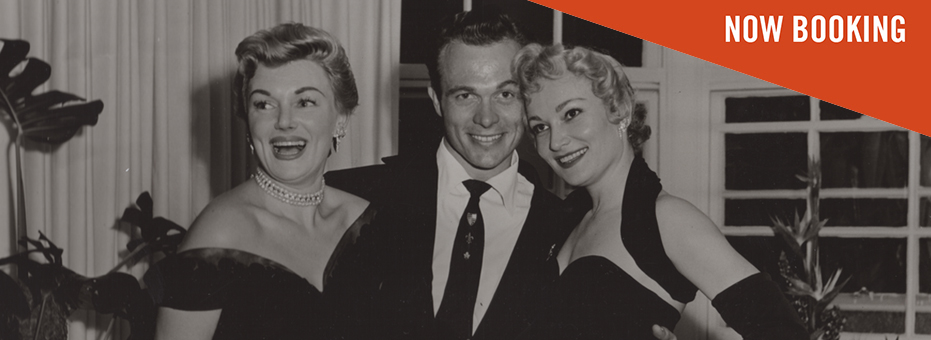 A black and white photo of a grinning young man in a smart black suit, standing between two glamorous blonde women in black dresses. The image is from Scotty and the Secret History of Hollywood.