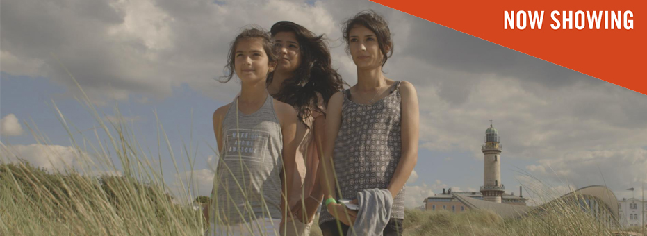 Three young Syrian women stand huddled together in the middle of some sandy, grass dunes in this still from Sky and Ground.