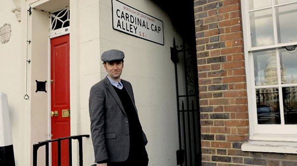 A retro images of a middle-aged white man in a 60s styled grey suit and wearing a flat cap to match. He stands between two buildings, where a small alleyway starts. A sign about him says 'Cardinal Cap Alley'.