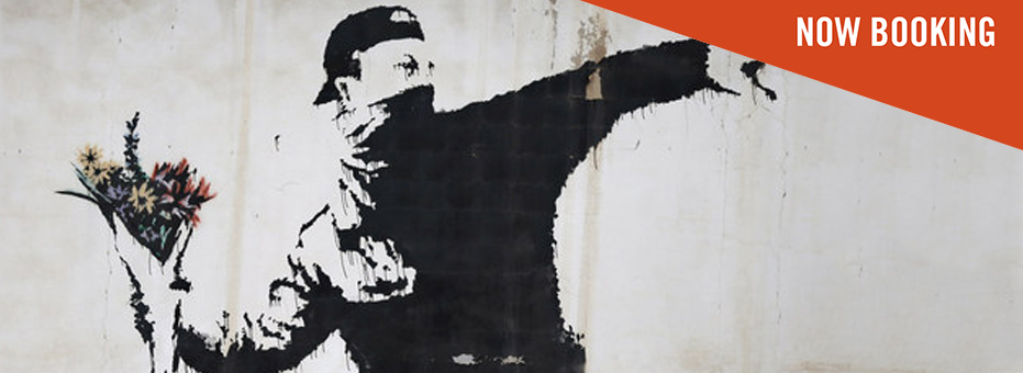 A graffiti-ed drawing of a young man in a black top and backward baseball cap. His gesture looks like he's going to throw a weapon, but he's actually holding a bouquet of flowers. The still is from the documentary The Man Who Stole Banksy.