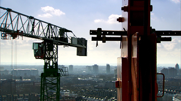 A beautiful image of the structure of two red-painted cranes, towering high above London on a clear, sunny day.