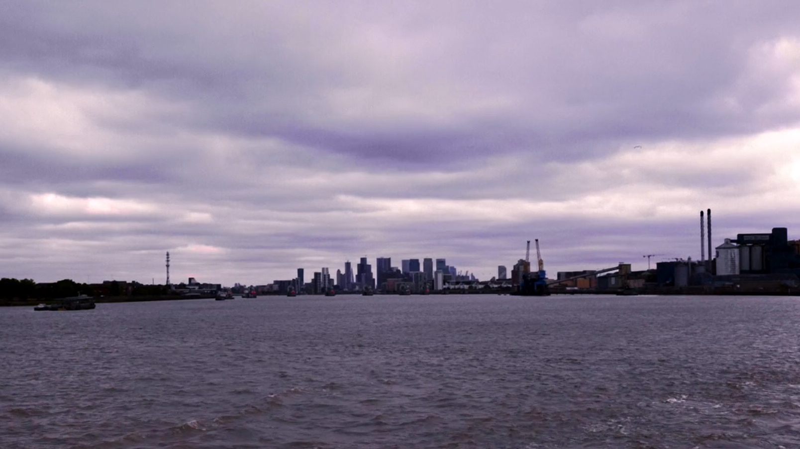 A picture of London's horizon, taken from a boat on the Thames itself, from East London. The buildings are small on the horizon, and the clouds are grey overhead.