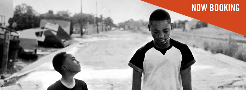 An incredibly beautiful black and white image of two you African American boys walking along a run-down street, which leads the eye down the background. An older, taller boy looks down at the ground, and a smaller boy looks expectantly up at the other.