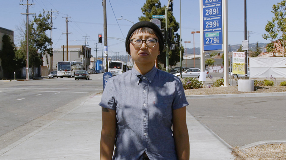 A young Asian American woman stands in a beanie hat and glasses at a crossroads in what looks like suburban L.A.