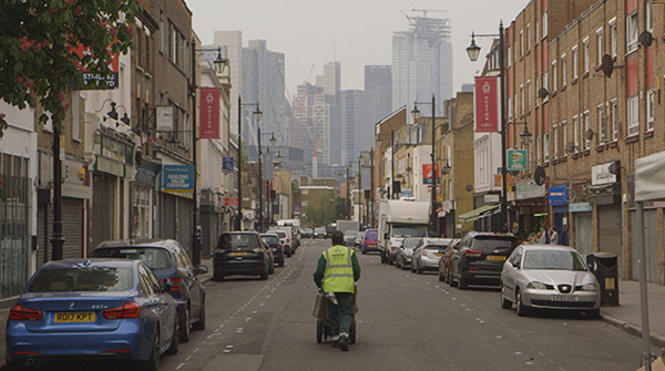 An image looking down London's Hoxton Street. In the middle of the road walks a street cleaner, wheeling his equipment. Off in the far distance you can see the high rises of the city looming at the end of this traditionally working-class street.